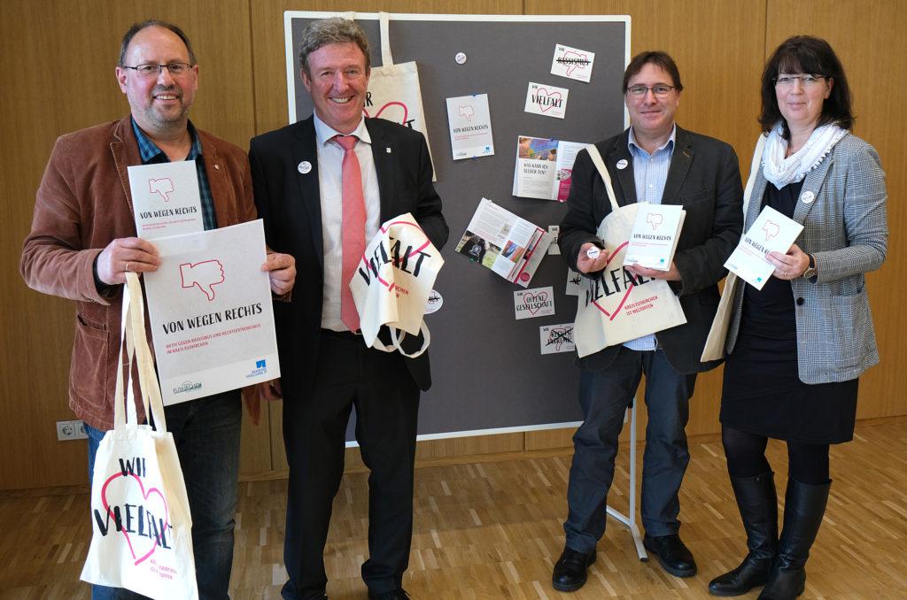 """Pressekonferenz für die Broschüre """"Von wegen rechts"""". Vier Menschen halten Broschüren und Taschen mit dem Weltoffen-Logo."""